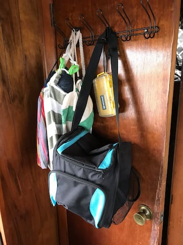 Small soft cooler. Beach towels and bags for collecting treasures on the beach.