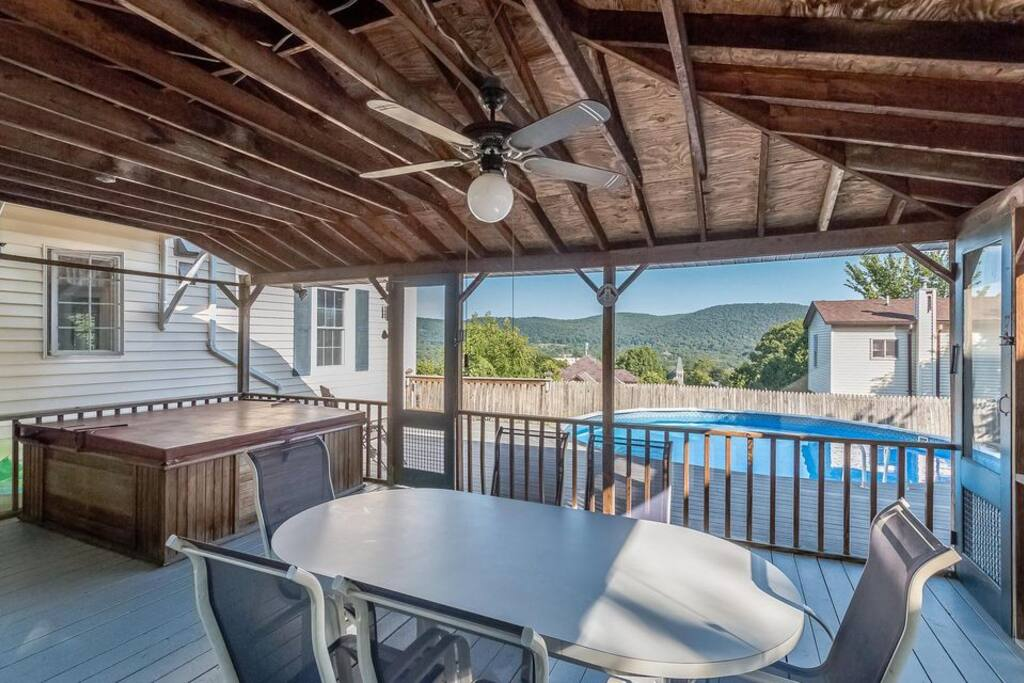 Screened in porch with hot tub.  Perfect for shade, no insects, and parties during inclement weather.