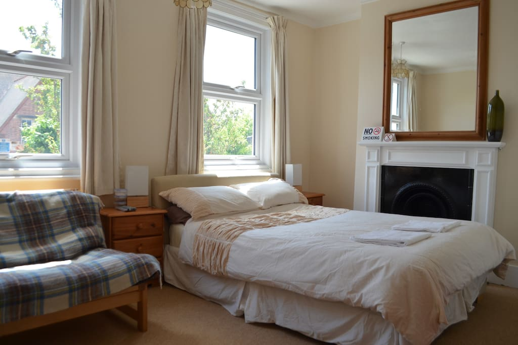 Double bedroom with bedside tables, lamps and mirror.