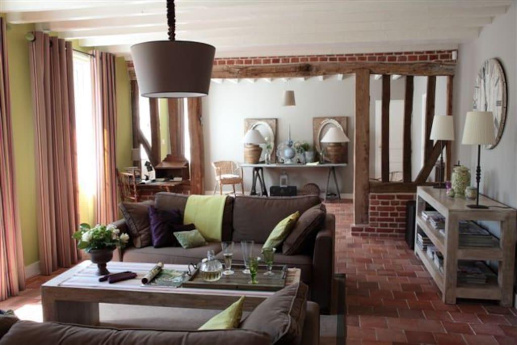 Avec ses larges fenêtres sur l'Abbaye,  le salon offre un volume généreux à partager en famille ou entre amis. Le fil conducteur taupe est twisté par un vert granny très normand !
