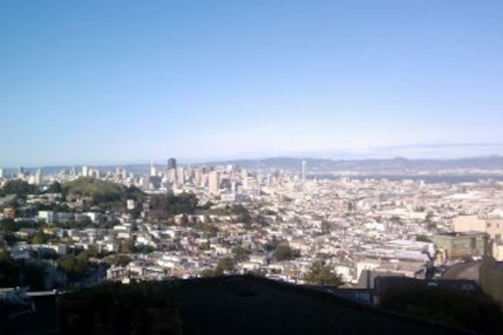The view from the living room/deck/office desk. AWESOME walks right outside your door. You can walk to the top of twin peaks, or down to Haight, or Castro area in 15 minutes. Or take public transportation as well. Street parking is safe and readily availa