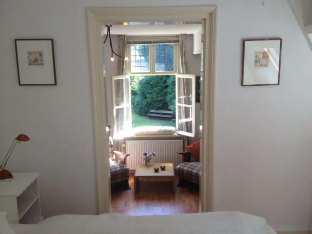 Een doorkijk vanuit de slaapkamer door het zitgedeelte naar een gedeelte van de tuin.