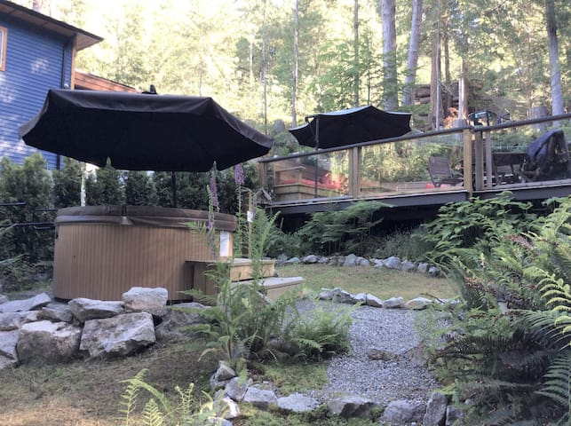 View of the hot tub and deck as you walk up the path to the cottage.  The umbrella and cedar trees behind create a private area to enjoy the forest.
