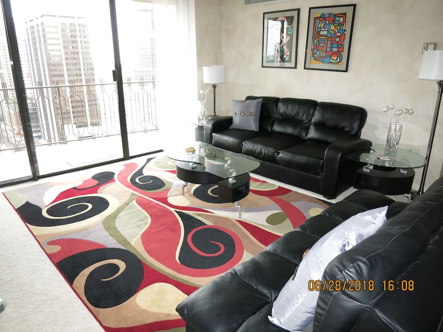 LIVING ROOM HAS CONTEMPORARY FURNITURE AND A COLLECTION OF ARTWORK