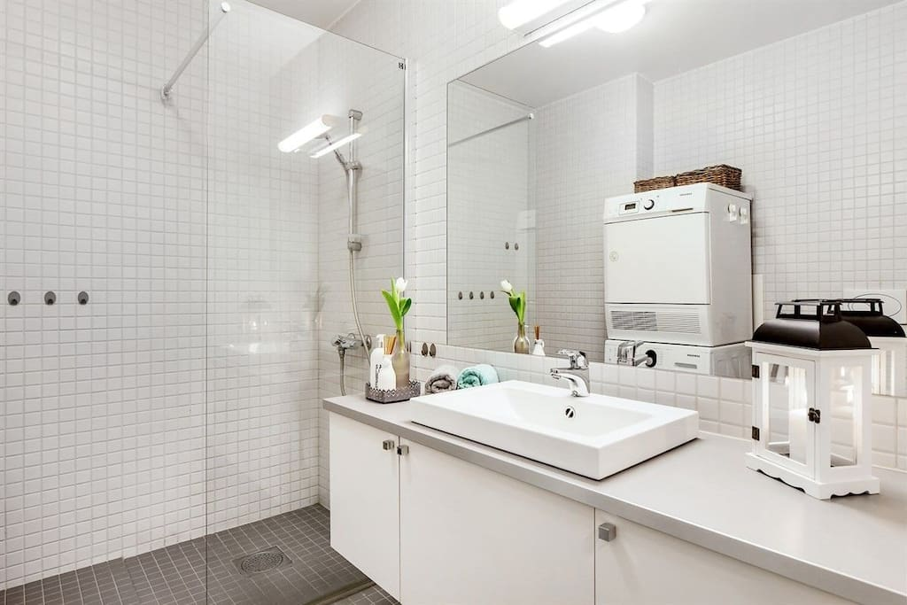 Bathroom with shower, washing machine and tumble dryer.