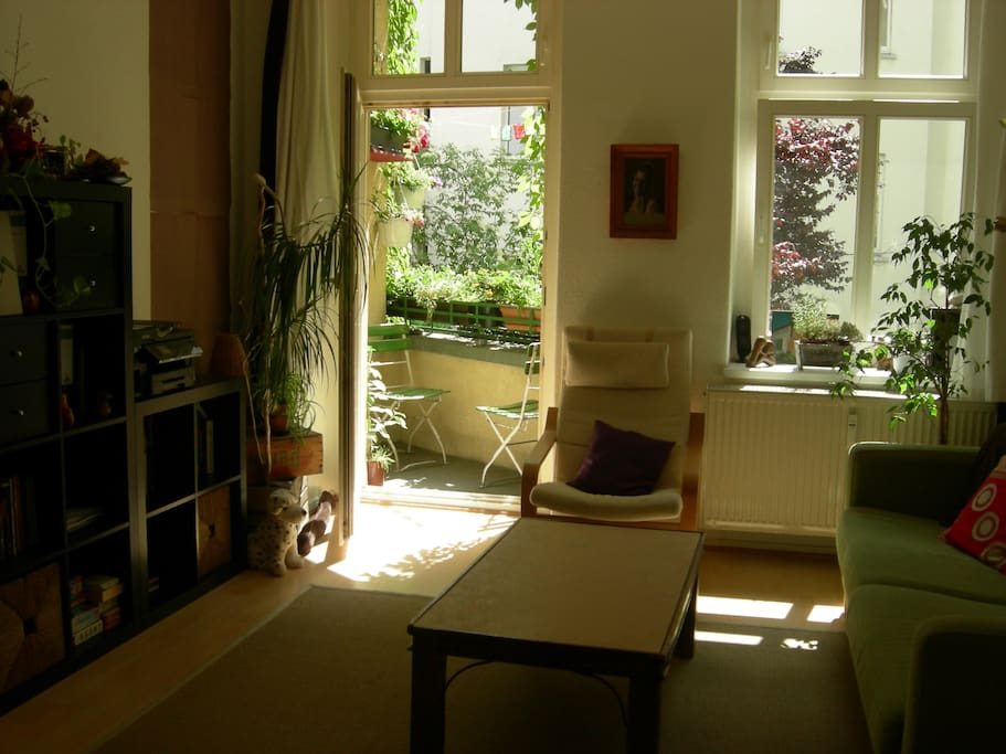 Living room with a very green, sunny balcony