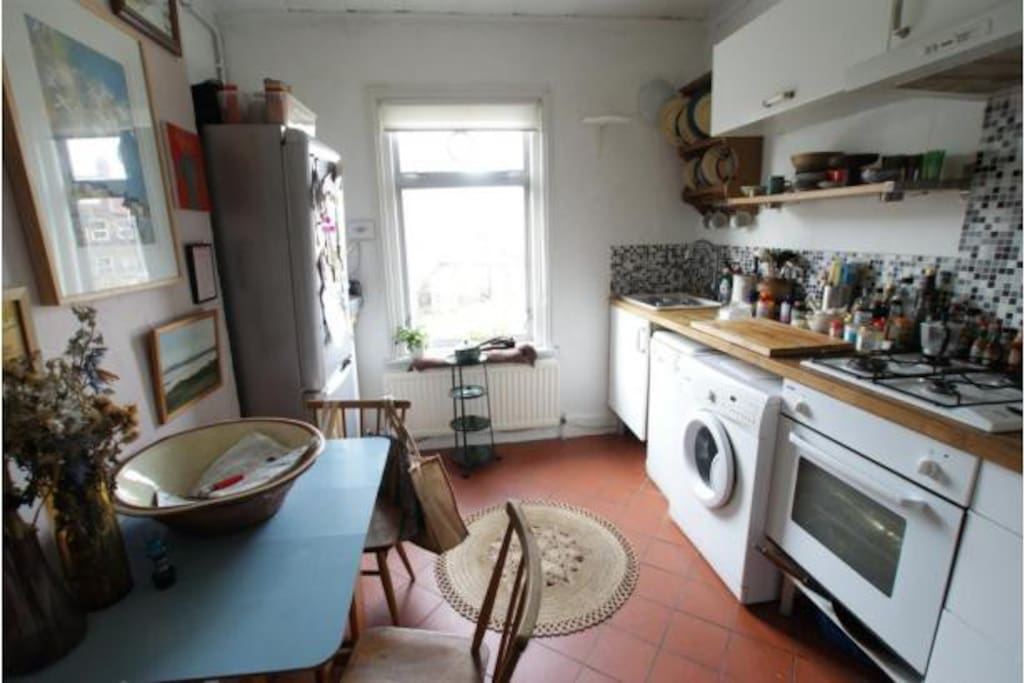 Kitchen with table and 3 chairs, electric oven, gas stove, washing machine, dishwasher.