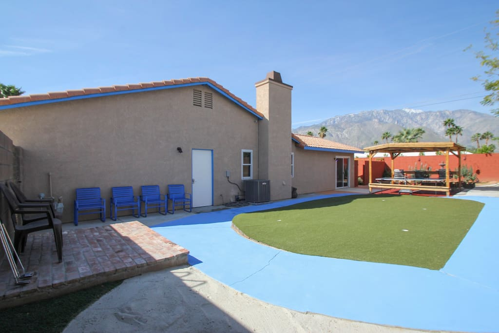 03 - Side yard putting green with sand trap and cabana with view of San Jacinto Mountains