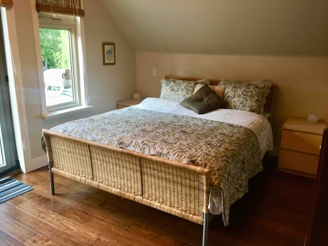 Comfortable Queen Size Bed in open concept space, overlooking the balcony & backyard