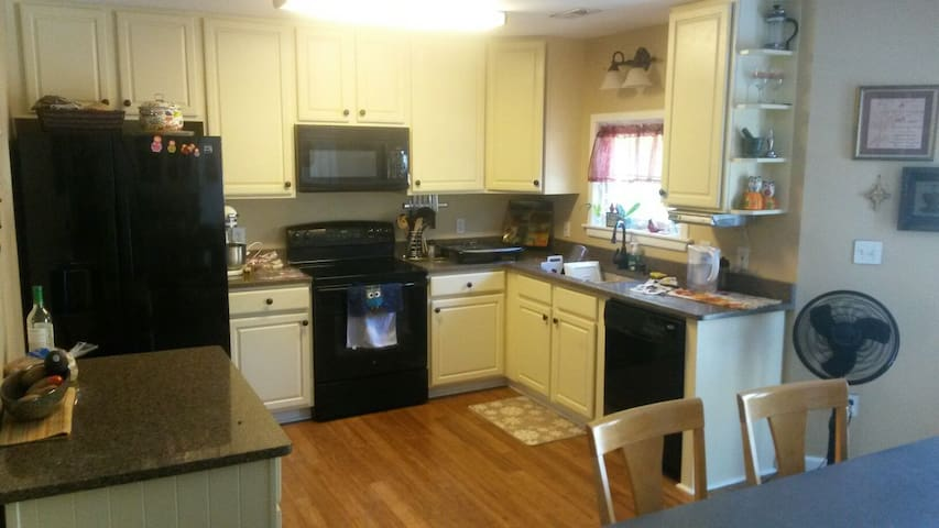 The kitchen with access to large back porch where additional outside seating is available.