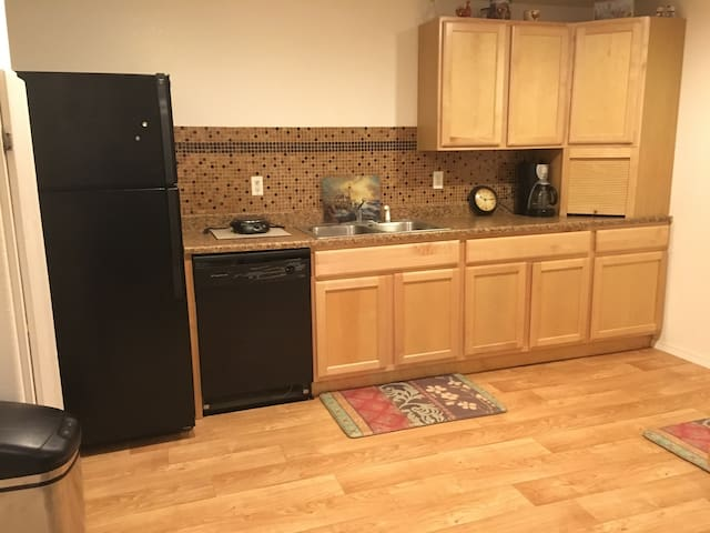 Full size refrigerator, dishwasher, hot plate, sink and dishes.