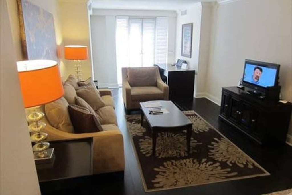 Living room with pullout sofa bed, club chair, entertainment center and convenient work desk