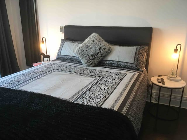 Main bedroom with beautiful wooden floors and access to outdoor balcony.