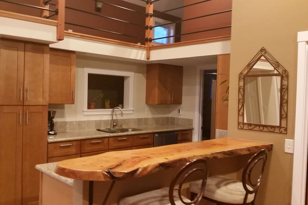 Beautiful kitchen with stainless appliances, heated slate floors and a hand made eating bar