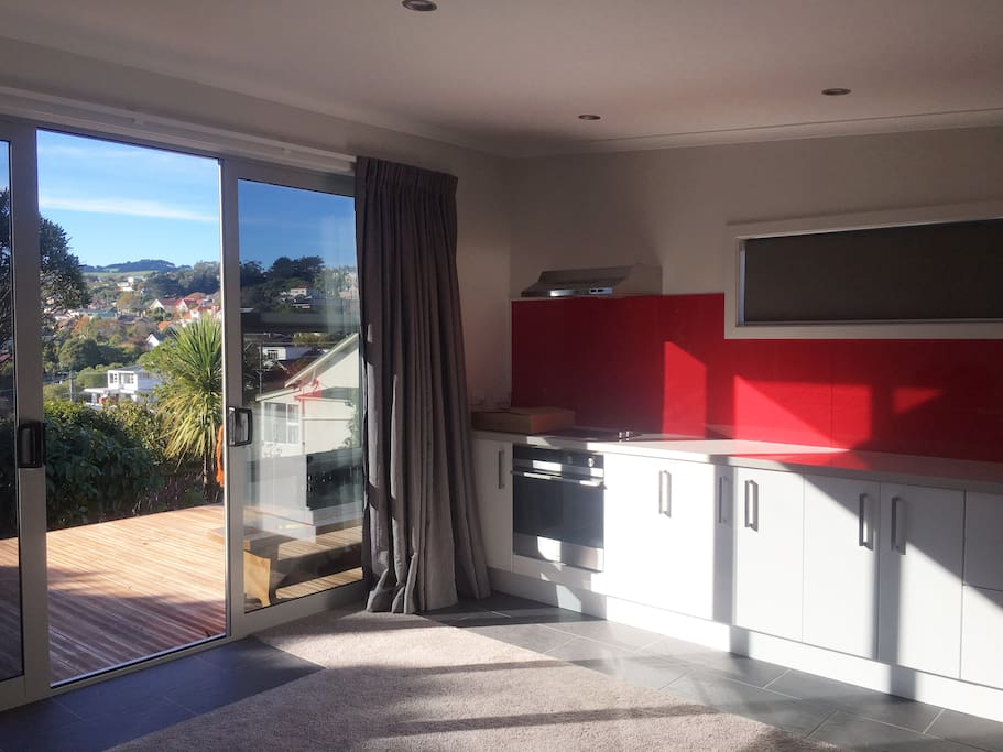 View from Lodge living area to Deck, Garden, and Otago Peninsula Hills