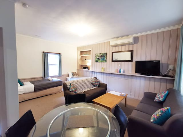 Unit 5, modern and stylish, with dining table and two single beds off to the side of the large lounge.
