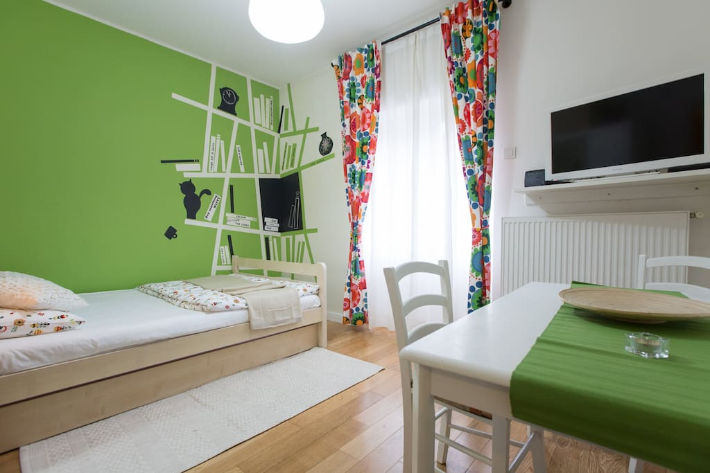 Living room with double bed, TV, dining table, exit to the terrace