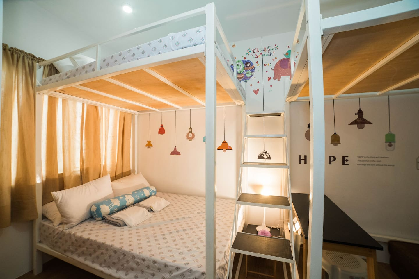2 loft type bunk beds to make the room look spacious. These beds each has double bed sized mattresses that can accommodate up to 6 guests. Below the other bunk is a mini-living area with a sofa bed that can accommodate 2 more guests.