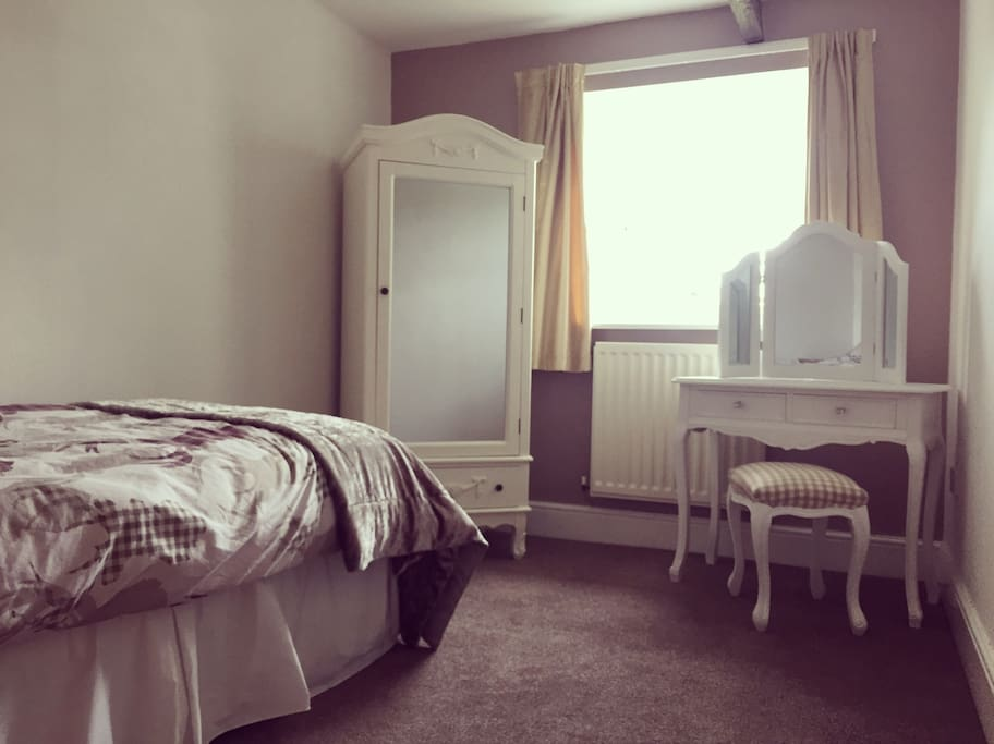 Double bedroom with fresh towels, slippers and dressing table. Coat hangers provided.