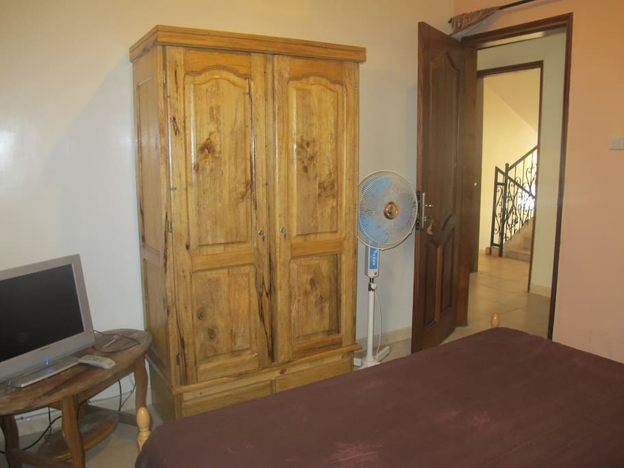 Another photo of bedroom (from a different angle- includes armoire, fan)