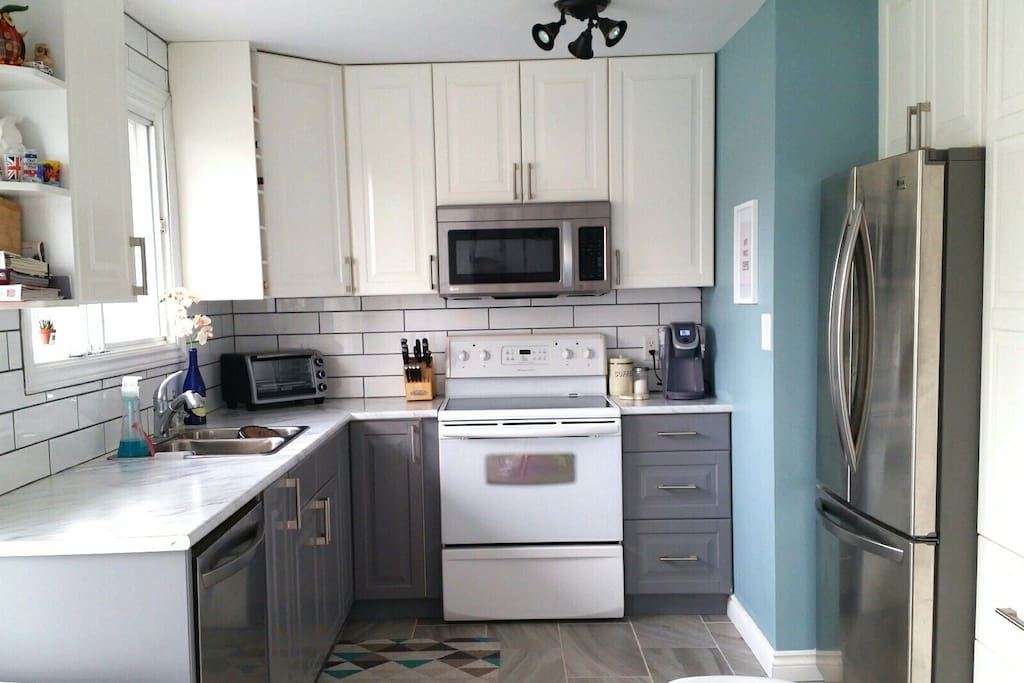 Newly renovated kitchen with double stainless steel fridge, dishwasher, toaster oven, microwave, and stove/oven. Laundry also available on site.