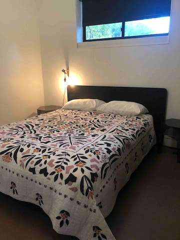 3rd Bedroom, featuring a comfortable queen sized bed and reading light. This bedroom has a full closet for storing all your stuff and shares a bathroom with the Master Bedroom
