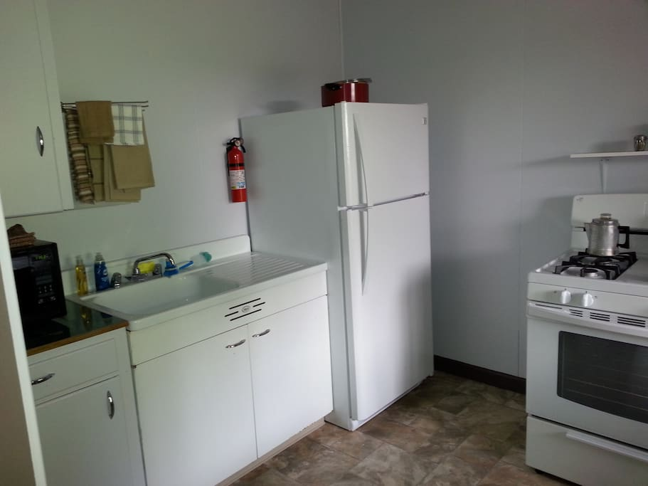 A full kitchen ready with breakfast supplies and cooking utensils.