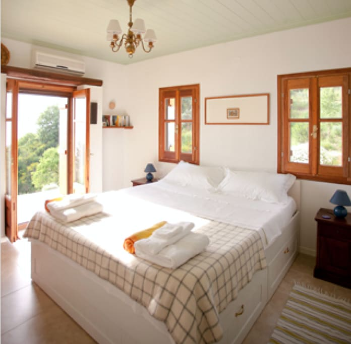 Two large en-suite bedrooms with a full view and double doors overlooking the garden and Aegean Sea.