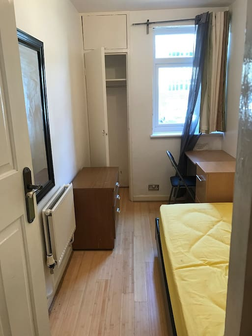 Single room with desk, plenty of storage and mirror.