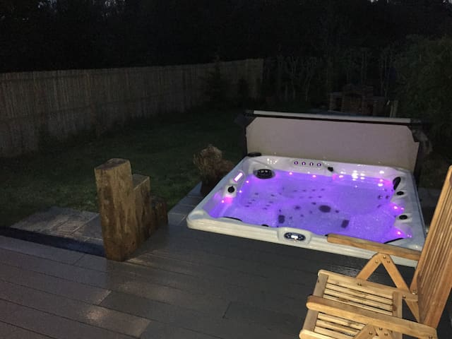 The hot tub is situated just off the decking and very close to The Cabin itself.