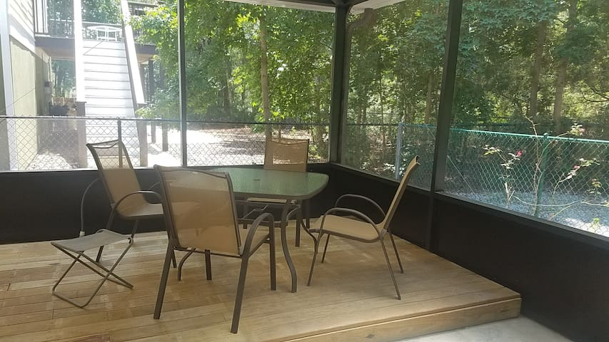 Table and four chairs inside the screened area.