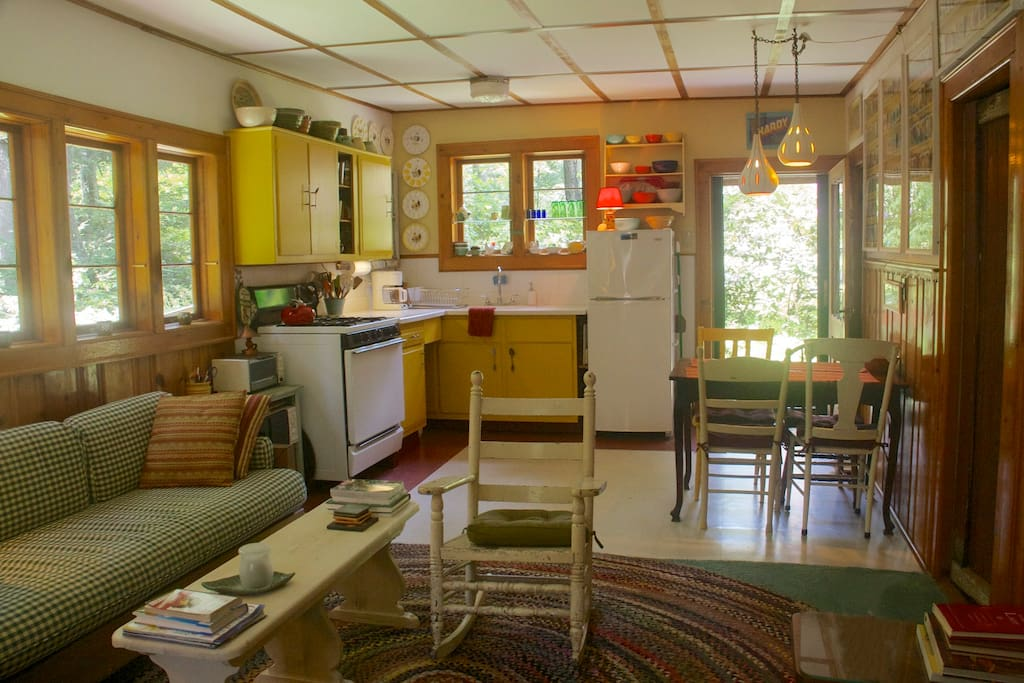Living room/kitchen with original 50s knotty pine and ceiling