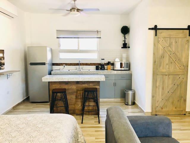 King size bed, kitchen and bathroom door.