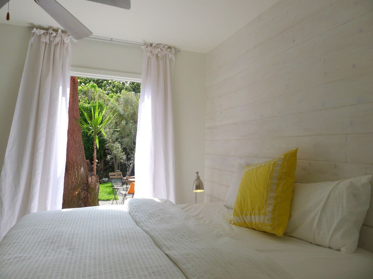 Reclaimed wood headboard wall and french doors lead to private front garden with zen fountain
