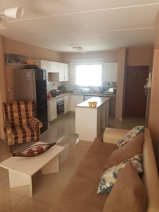 Kitchen fully equipped with washing machine. Open plan lounge and kitchen.