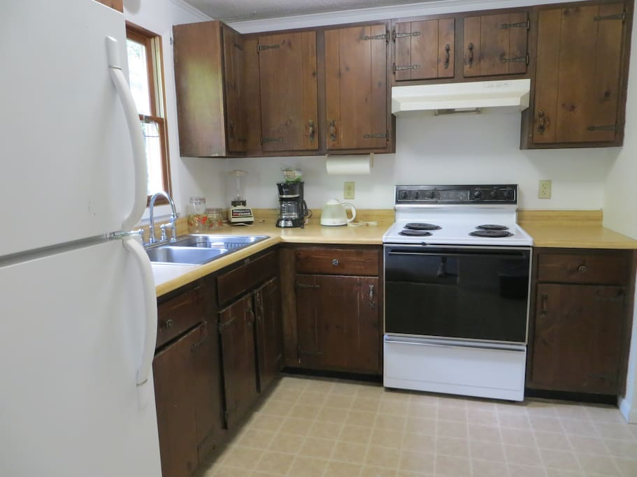 kitchen set up to use with a microwave, coffee maker, blender, plates, glasses, silverware, etc.