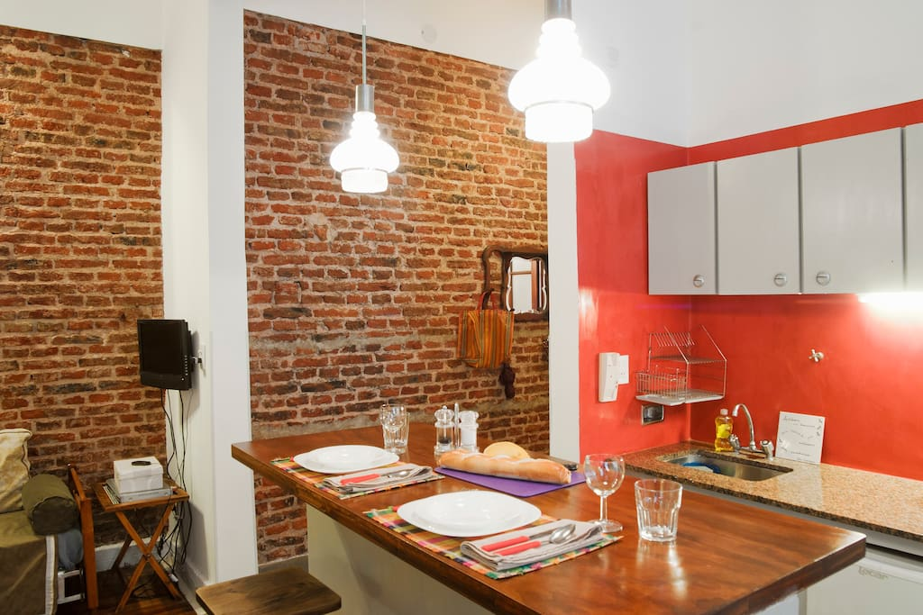Exposed brick walls in the living room and foyer with polished cement in the kitchen.