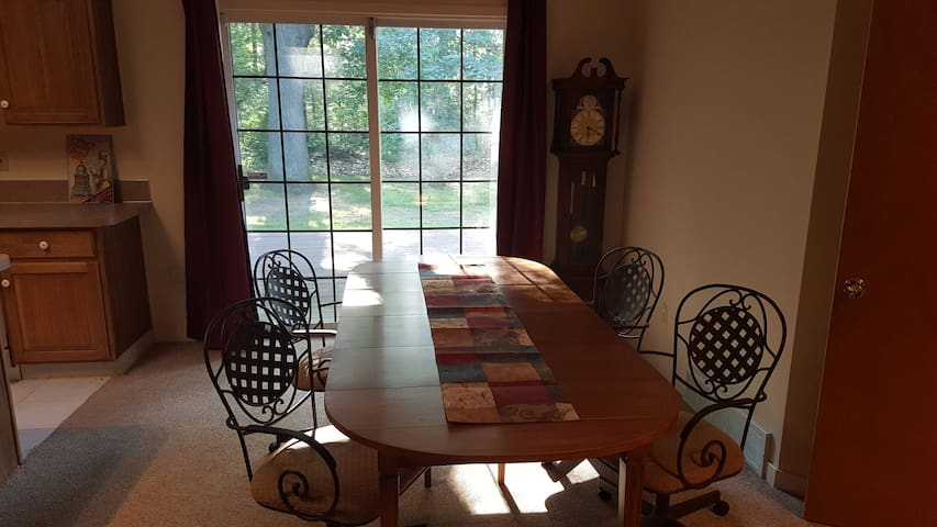 Antique dining room table looking out onto the back deck and the woods.