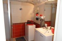 la salle d'eau avec douche, meuble vasque et machine à laver le linge et wc