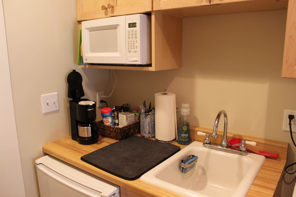 The well stocked kitchenette includes a coffee maker (coffee + tea provided), microwave, refrigerator, sink, and toaster oven.