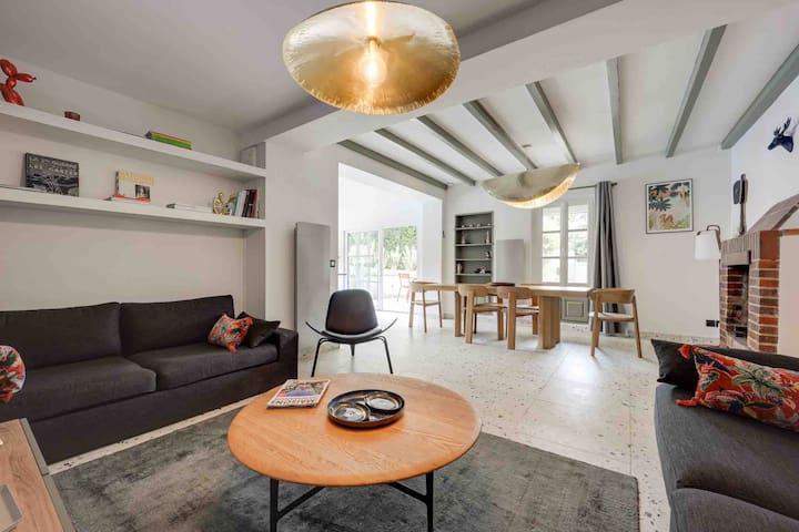 Grand espace de vie ouvert de 60m2 de plain-pied. Salon avec cheminée, salle à manger jusqu'à 12 places, cuisine ouverte sur la terrasse et la piscine