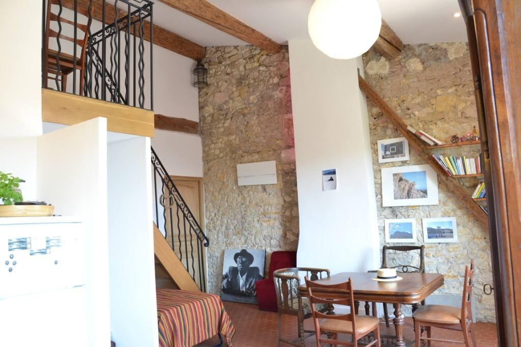 Vue du salon. Grand mur en pierres, tomettes provençales, fer forgé, poutres en mats de marine: refait à neuf en 2012, dans le respect de cet immeuble du XVIIIeme.