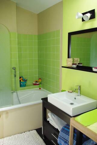 salle bain a l'étage avec baignoire, une vasque et table à langer