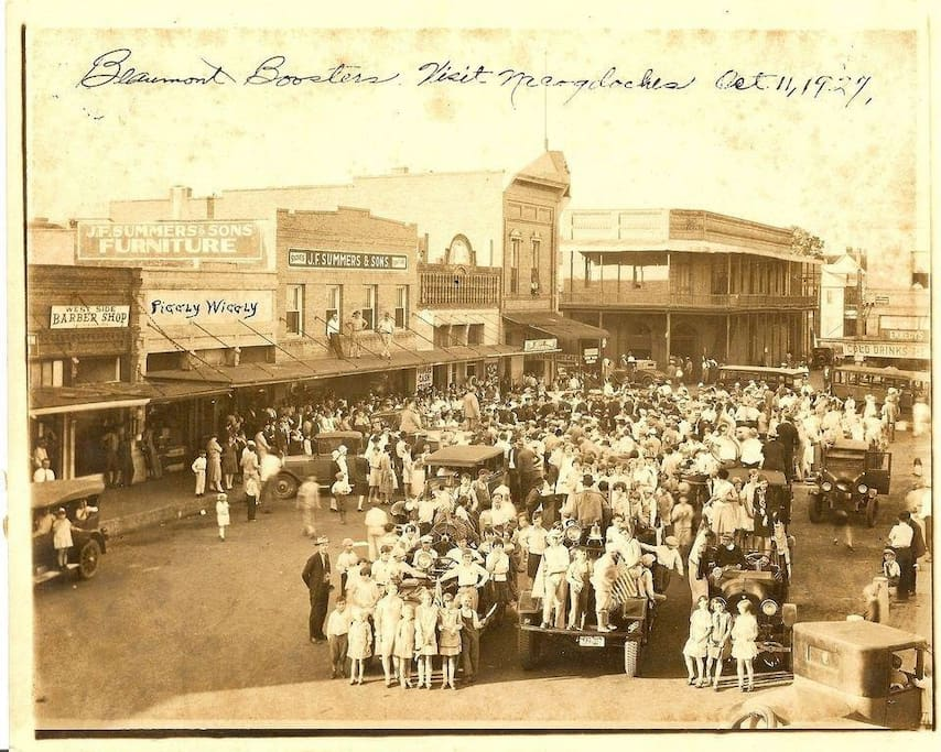 In 1927 the Beaumont Boosters visit Nacogdoches.  The Cox building is the 2nd from the right with the wrap-around balcony.