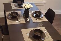Shared dining room in kitchen equipped with brand new plates, cups, silverware and utensils.
