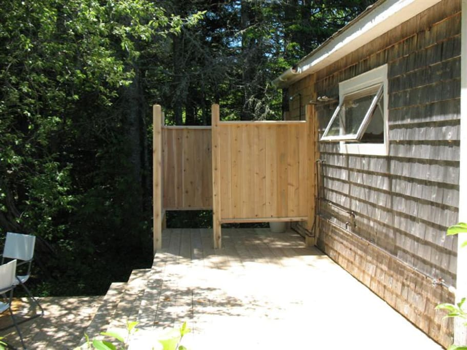 Private outdoor shower on the deck behind the cabin.