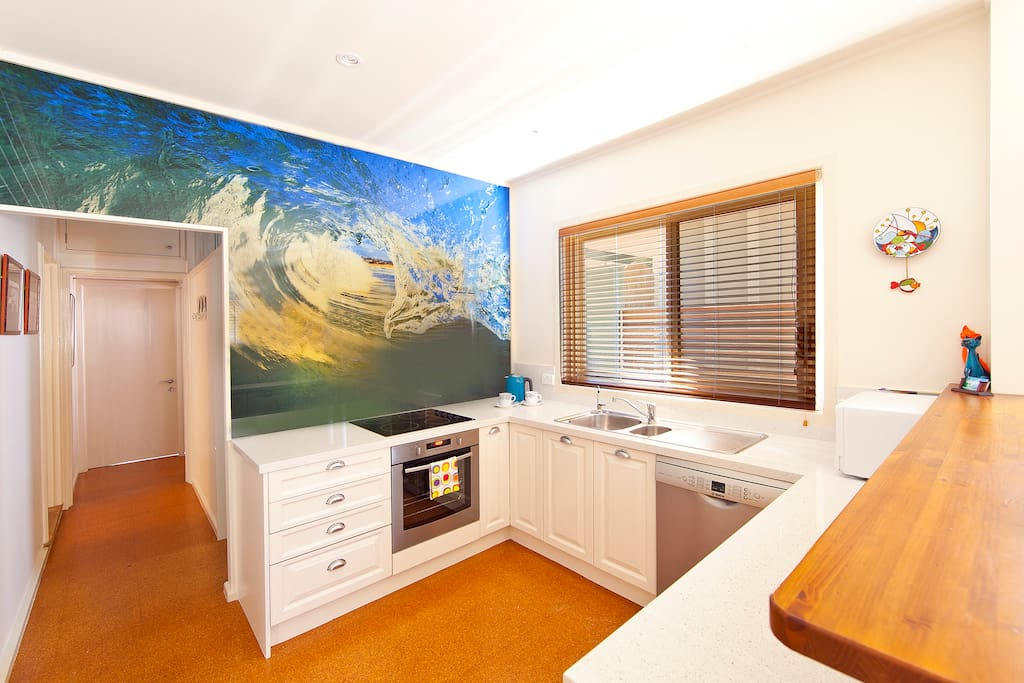 Modern kitchen featuring stunning wave taken at Curl Curl Beach (photo by Lime Photography)