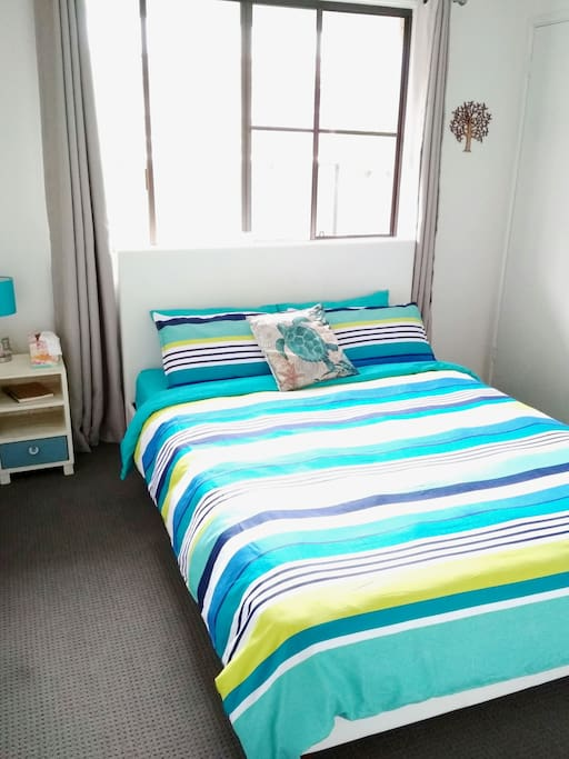 Your bedroom features a queen sized bed with a comfy duvet and medium pillows. There is a ceiling fan, a heater and floor fan in the closet.
