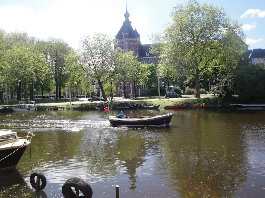 View from the red bench: a little boat with the Amsterdam flag goes by...
