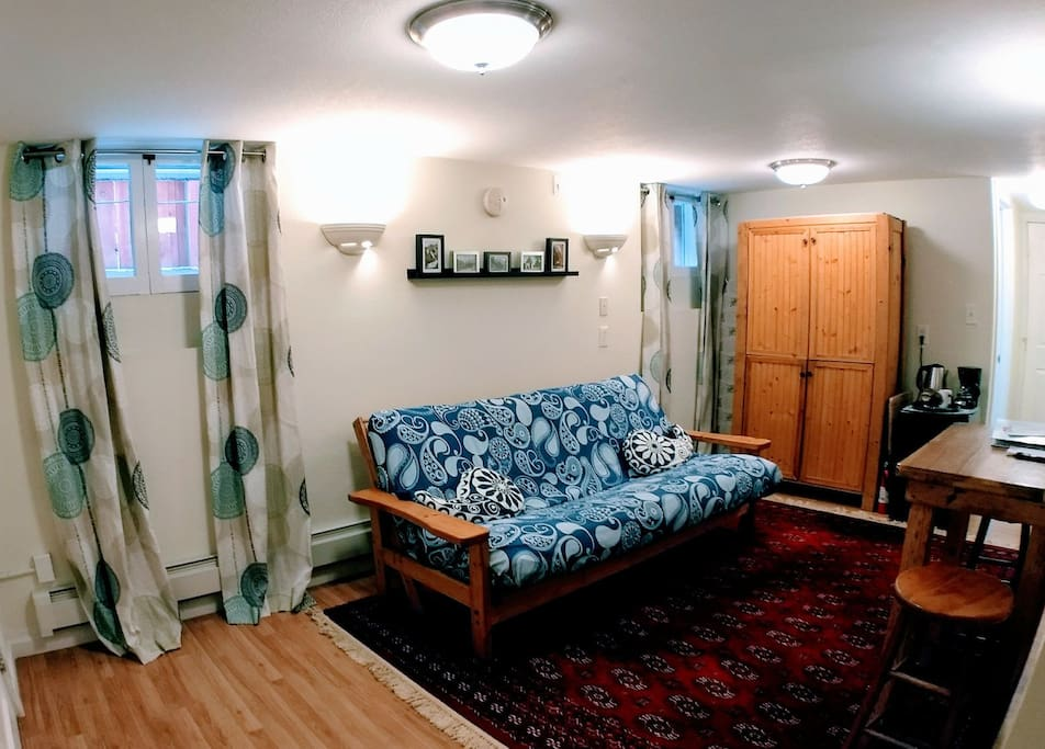 Our cozy, bright living area. Our futon is great for lounging and also serves as an extra bed should you need it.